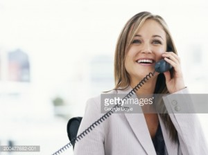 young-businesswoman-using-telephone-in-office-smiling-picture-id200477682-001